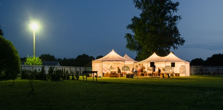 outdoor event: Wedding tent on the lawn at night