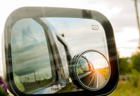 espejo: puesta del sol reflejada en el espejo de un coche Foto de archivo