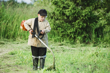 grass cutting: Young boy mowing grass Stock Photo