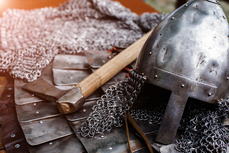 Iron helmet in armor and battle ax with shallow depth of field