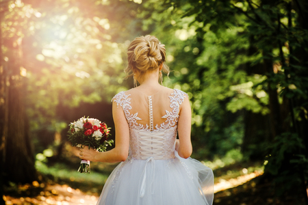 back of the bride against the background of foliage and sunlight