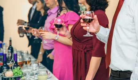 people hold wine glasses in their hands at shallow depth of field