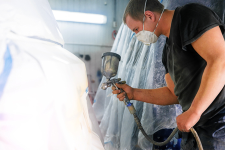 man with a spray gun in his hand Imagens
