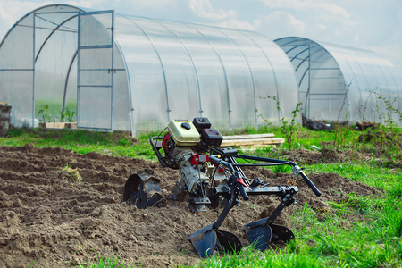 gasoline cultivator on the background of greenhouses for growing vegetables 写真素材