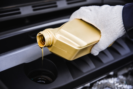 pouring engine oil into a car engine