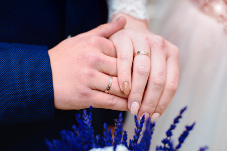 hands of newlyweds with rings over blue flowers 写真素材