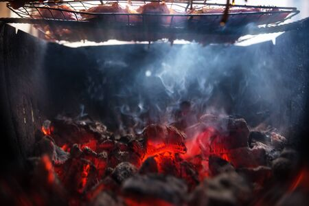 hot coals and meat above them with a shallow depth of field Stock Photo