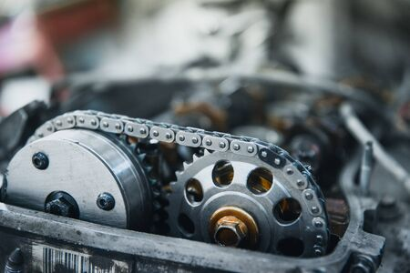 chain and gears of a car engine with a shallow depth of field