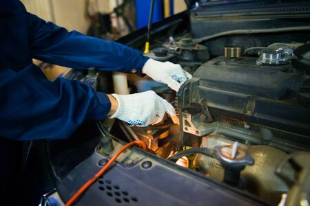 worker repairs car engine with shallow depth of field