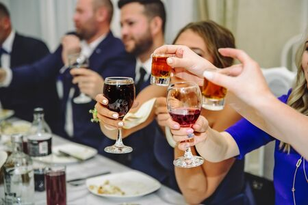 outstretched hands with glasses clink glasses at the festive table with a shallow depth of field Stock Photo