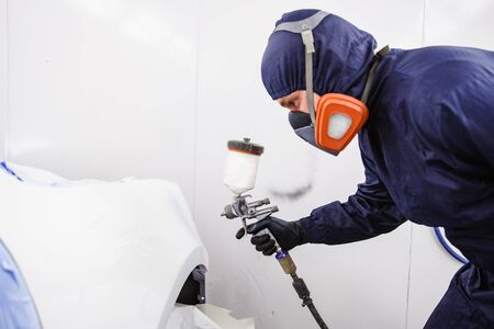 worker with spray gun in spray booth Banco de Imagens