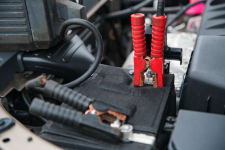 clamping the charger and starting device on the positive terminal of the car battery at shallow depth of field Imagens