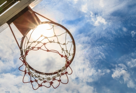 Looking up basketball hoop with a blue sky. Stock Photo