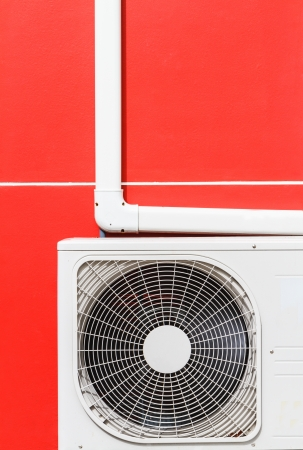 conditioned: air conditioner machines on red wall