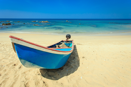 traditional long tail boat stand on the beach in Thailand