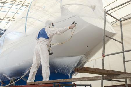 hombre pintando: El hombre rociado de pintura para el barco