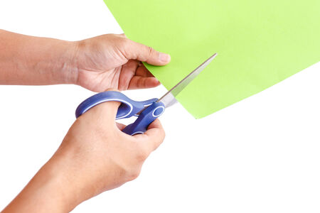 Hand using scissors cuting green paper, isolated on white background photo
