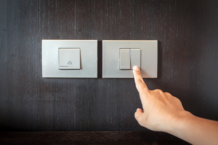 hand pressing electronic-light switch Stock Photo