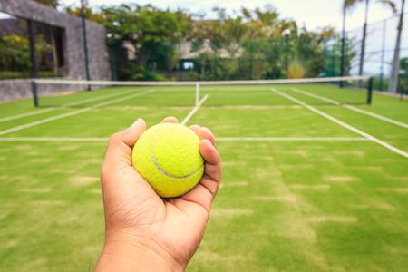 Hand holding tennis ball photo