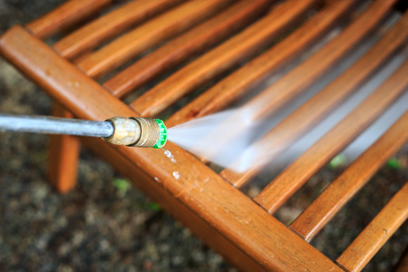 pressure washing: Wooden chair cleaning with high pressure water jet