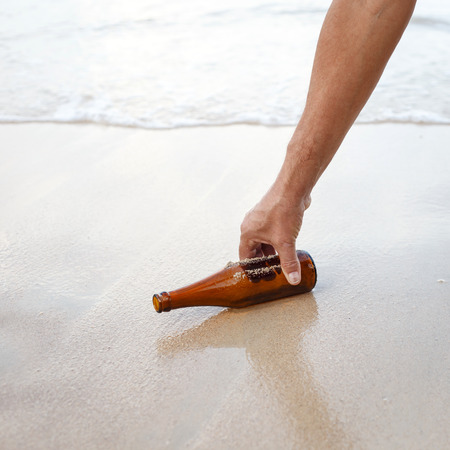 Hand holding glass bottle at the beach photo