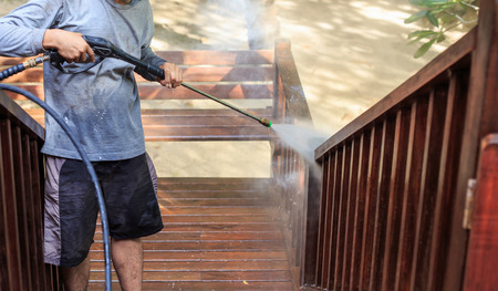Thai man do a pressure washing on timber photo