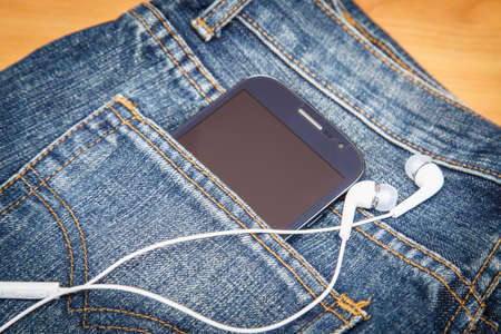 Close up of smartphone in denim jeans pocket photo