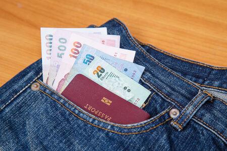Thailand Passport and money in denim jeans pocket photo