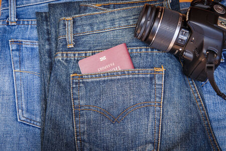 Close up of Passport in denim jeans pocket with a camera photo