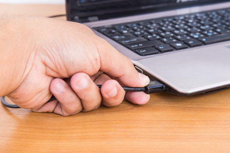 Hand holding and plug USB cable to laptop
