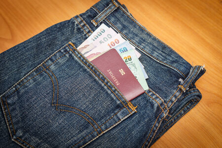 Passport and money in denim jeans pocket photo