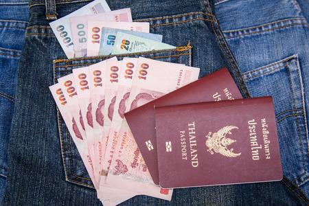 Thailand Passports and money in denim jeans pocket photo