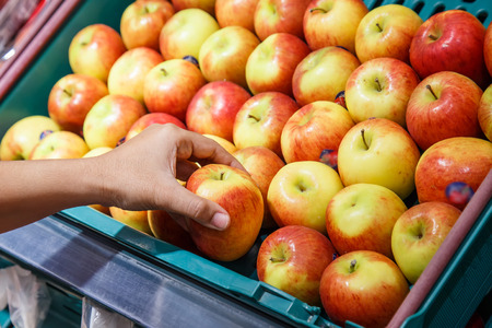 Hand holding apple in department store photo