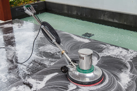 Thai people cleaning black granite floor with machine and chemical Banque d'images