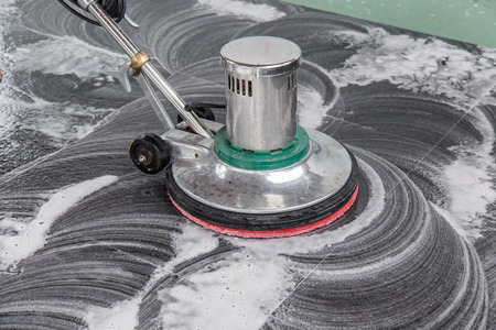 Thai people cleaning black granite floor with machine and chemical Stock Photo
