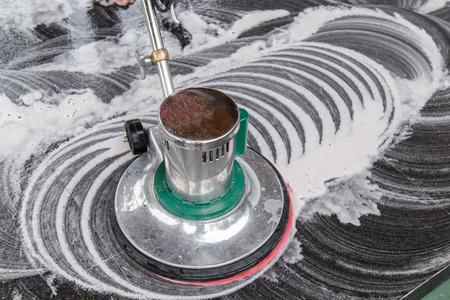 Thaise mensen aan het schoonmaken zwarte granieten vloer met machine en chemische