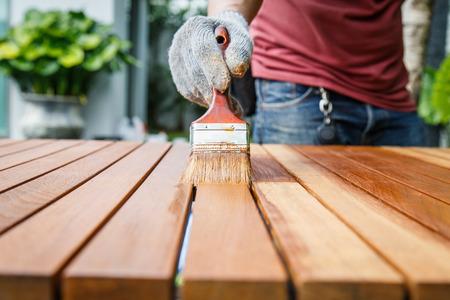 menuisier: Pinceau � la main et la peinture sur la table en bois