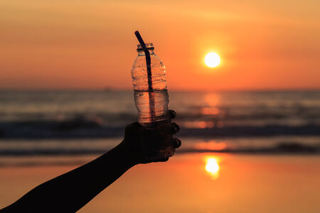 people drinking water: Silhouette of hand holding drinking water bottle at the beach in sunset time
