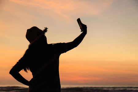 Silhouette of Thai Woman using smartphone at the beach in sunset time photo