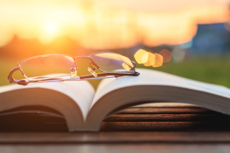 Close up glasses and book on table in sunset time Stockfoto