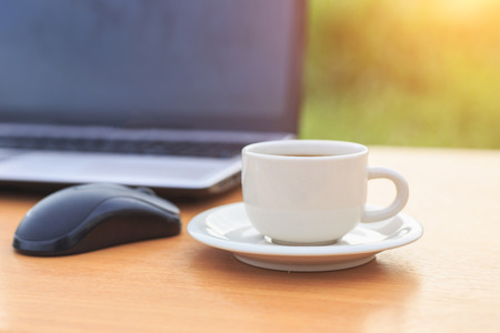 Close up coffee cup and laptop on the table in the morning photo