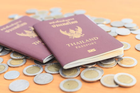 Close up Thailand passport and coin on the table photo