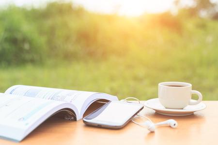 Kaffeetasse und Buch auf dem Tisch in der Früh
