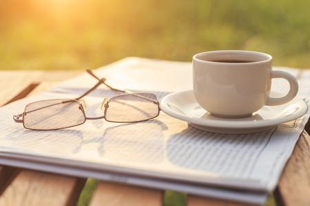 朝の新聞でメガネとテーブルの上のコーヒーを閉じる 写真素材