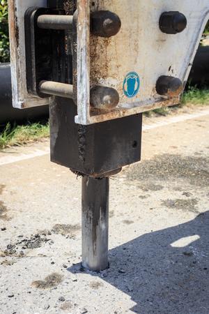 Excavator breaking street asphalt with hydrohammer drill at repairing roadwork photo