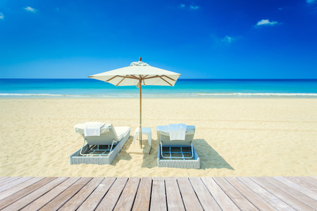 Sun umbrella and sun loungers stand at the beach in Phuket, Thailand