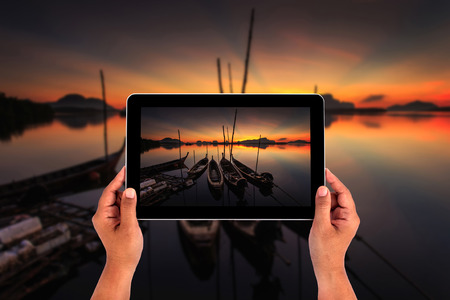 Hands holding tablet taking pictures photo