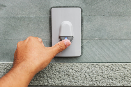 Hand pressing doorbell Stock Photo