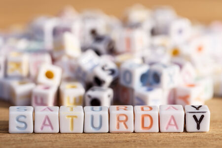 Saturday written in letter beads on wood background photo