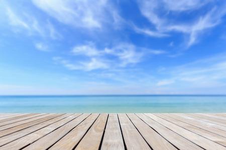 Tarima de madera gris y playa tropical